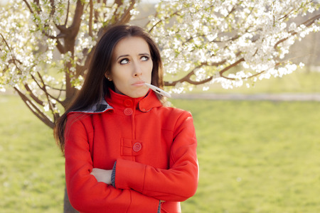 flue season: Sad Woman with Thermometer in Spring Blooming Decor Stock Photo