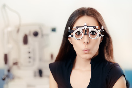 Funny Girl at Ophthalmological Exam Wearing Eye Test Glasses Foto de archivo