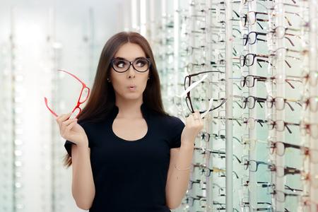 광학 스토어에서 안경 프레임을 선택하는 여자 스톡 콘텐츠