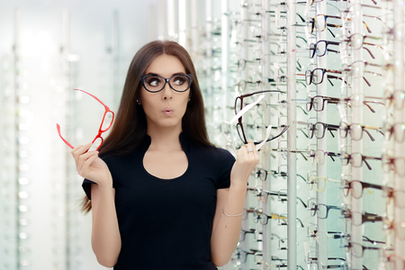 Woman Choosing Eyeglasses Frames in Optical Store