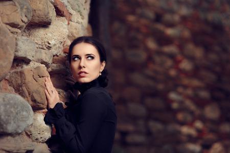 castello medievale: Scared principessa Vicino Castle Wall Archivio Fotografico