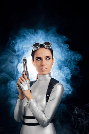 spy girl: Woman in Silver Space Costume Holding Pistol Gun Stock Photo