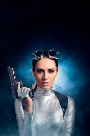 catsuit: Woman in Silver Space Costume Holding Pistol Gun Stock Photo