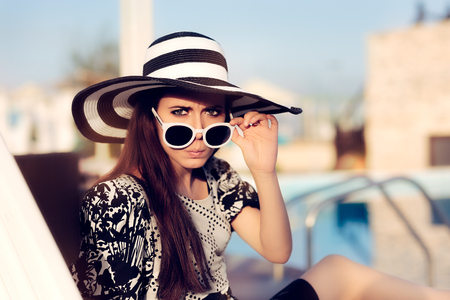 celebrities: Surprised  Girl With Sunglasses and Hat Sitting on Sun Chair Stock Photo