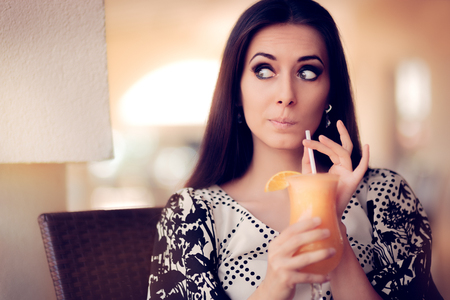 intrigued: Surprised Woman With Orange Juice in a Restaurant Stock Photo