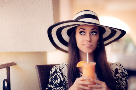 a straw: Surprised Woman With Orange Juice in a Restaurant Stock Photo