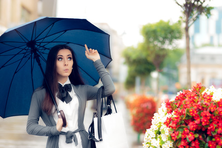 torrential: Woman Looking for a Taxi in Rainy Weather Stock Photo