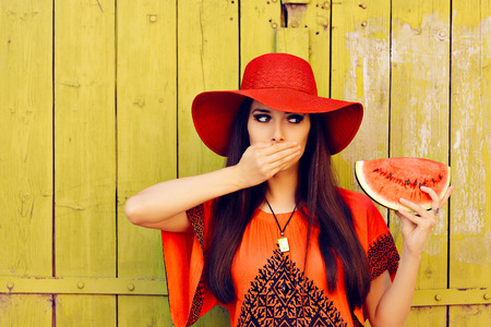 summertime: Surprised Woman in Red Hat with Watermelon Slice