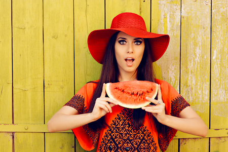 intrigued: Surprised Woman in Red Hat with Watermelon Slice