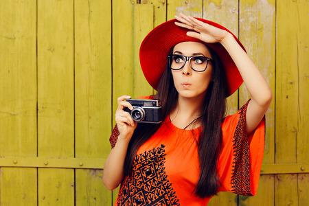 intrigued: Funny Girl with Retro Photo Camera and Red Sun Hat