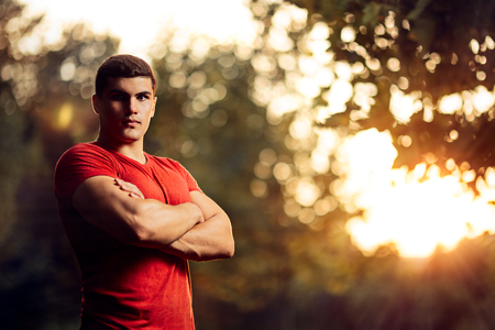 Handsome Athletic Man Standing Outside in Nature Stock Photo