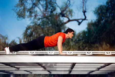 pushup: Athletic Man in Push-up Plank Position Training