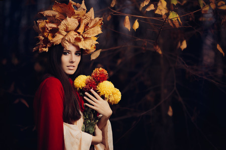 exquisite fairy: Beautiful Woman With Autumn Leaves Crown Holding Flowers Stock Photo