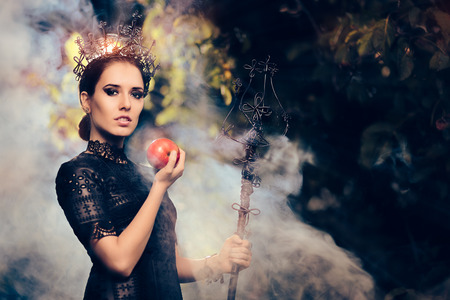 Evil Queen with Poisoned  Apple in Misty Forest 版權商用圖片 - 62925378