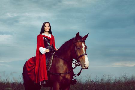 Schöne Prinzessin mit roten Umhang auf einem Pferd