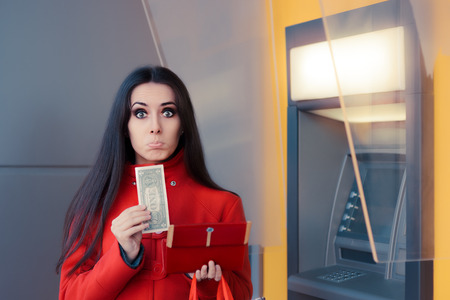 christmas debt: Broke Woman Holding One Dollar in Front of an ATM