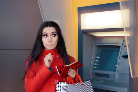 spender: Funny Shopping Woman Holding a Penny in front of an ATM Stock Photo