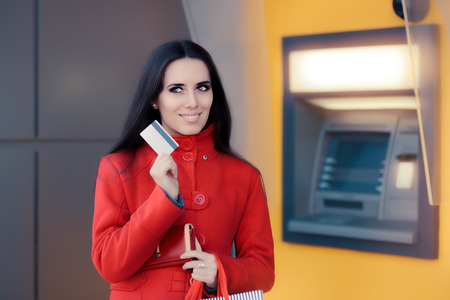 bankomat: Happy Shopping Woman Holding Credit Card in front of an ATM Stock Photo