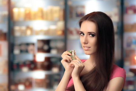 eau de toilette: Beautiful Girl Testing Perfume in a Cosmetics Shop Stock Photo