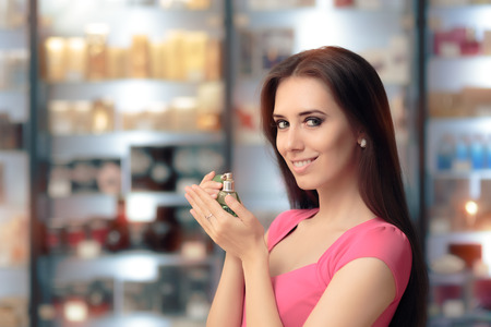 fragrant scents: Smiling Woman Holding Retro Perfume Bottle