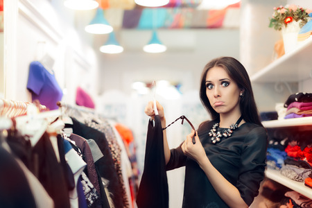 Woman Checking Price Tag on Sale in Clothing Store Standard-Bild