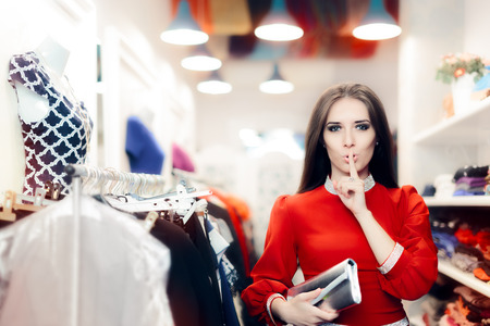 Elegant Woman Keeping a Secret in Fashion Store Stock Photo