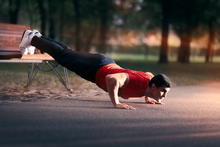 Fitness Man doing a Bench Press Up Outside