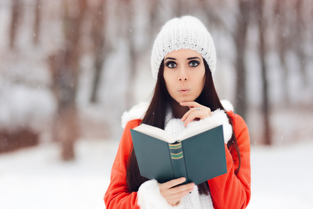 Surprised Woman Reading a Book Outside in the Snow