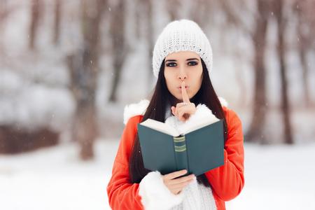 silencio: Mujer del invierno con el dedo en sus labios que sostiene un libro Foto de archivo