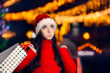 caras emociones: Tired Christmas Woman With Shopping Bags Foto de archivo