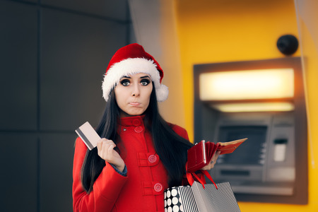 checking account: Christmas Woman Checking her Wallet in Front of a Bank ATM