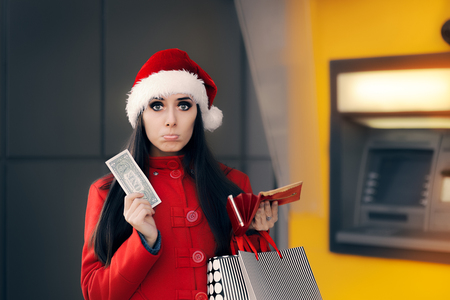 indebted: Christmas Woman Holding One Dollar in Front of an ATM