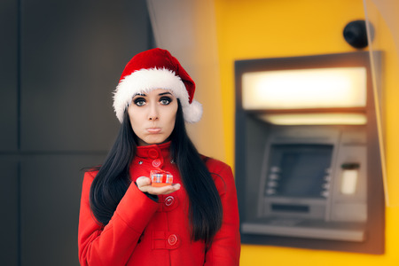 bankomat: Disappointed woman with Small Gift Box in Front of an ATM