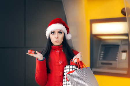 Girl holding Small Gift Box and Shopping Bags in front of an ATM