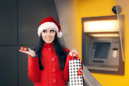 automatic transaction machine: Muchacha que sostiene la pequeña caja de regalo y bolsas de la compra frente a un cajero automático