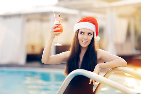 flirty: Flirty Christmas Woman with Cocktail at the Pool Stock Photo