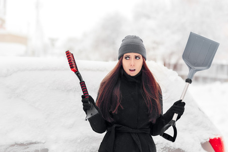 Girl with Brush and Shovel Removing Snow from the Car Stockfoto
