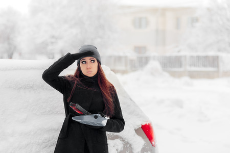 Girl with Brush and Shovel Removing Snow from the Car Stock Photo