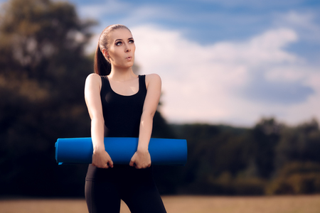 Excited Pilates Girl with Yoga Mat Standing Stock Photo