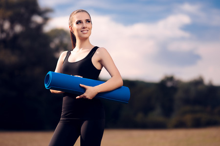 Pilates Girl with Yoga Mat Standing Outdoor in Nature