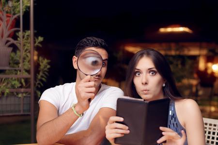 Copain et copine Surpris par le projet de loi de restaurant cher Banque d'images