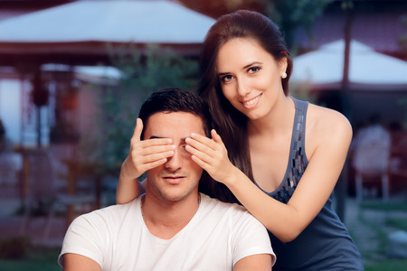 impression: Woman Covering Man's Eyes Taking him by Surprise on a Blind Date Stock Photo