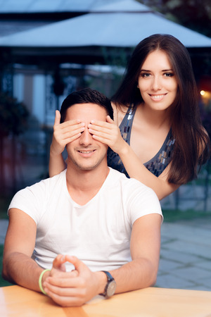 blind date: Woman Covering Man's Eyes Taking him by Surprise on a Blind Date Stock Photo