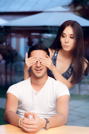 covering: Woman Covering Man's Eyes Taking him by Surprise on a Blind Date Stock Photo