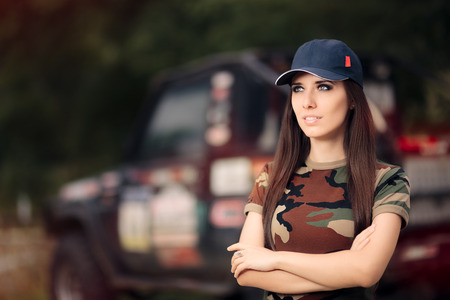 Female Driver in Army Outfit Next to an Off Road Car