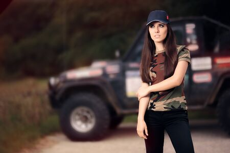 role models: Female Driver in Army Outfit Next to an Off Road Car