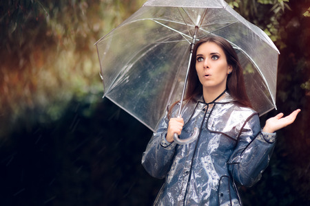 Surprised Woman in Raincoat with Transparent Umbrella