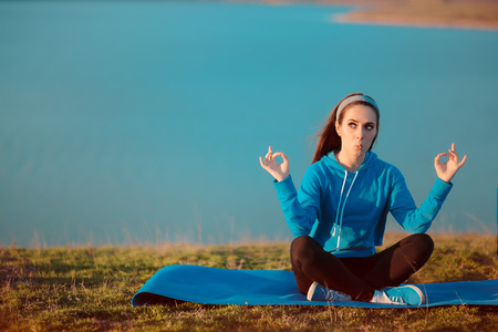 Funny Girl Meditating on Yoga Mat in Nature Stock Photo