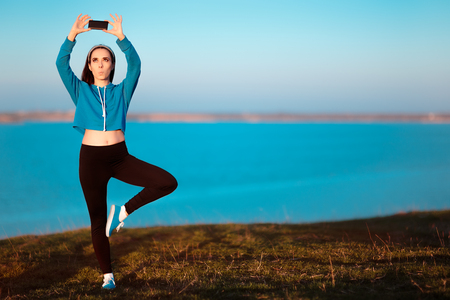 Girl in Yoga Pose Taking a Selfie Outside in Nature