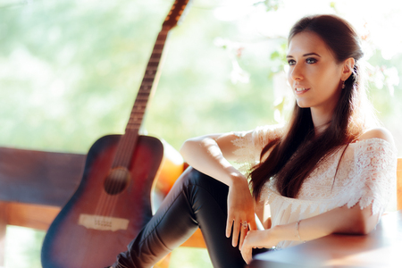 showbusiness: Portrait of a Beautiful Woman next to Her Guitar